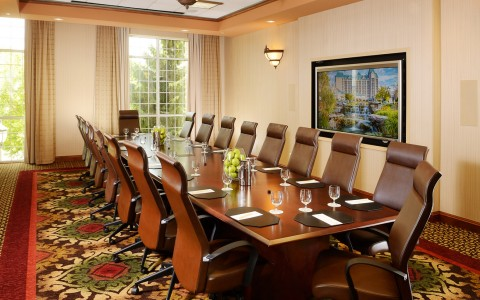 Long wooden table for meeting with chairs