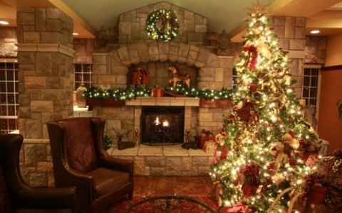 Fireplace decorated with lights and wreath with Christmas tree