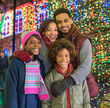 family in front of christmas light display events