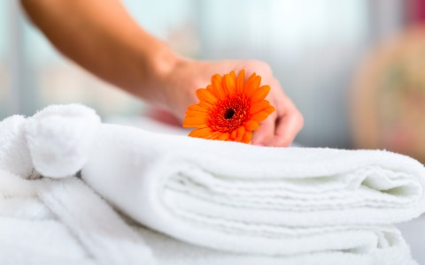 Hand placing orange flower on top of a folded towel
