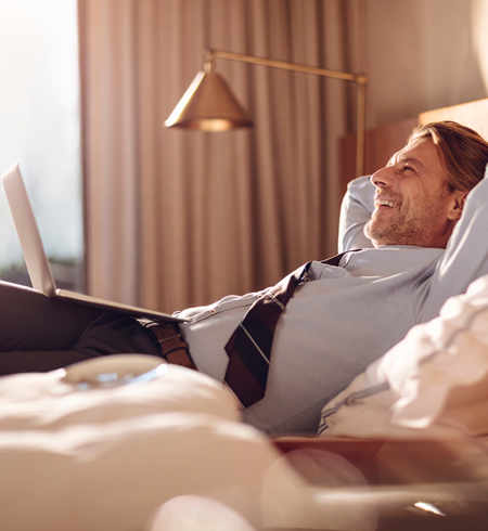 Man smiling laying in bed