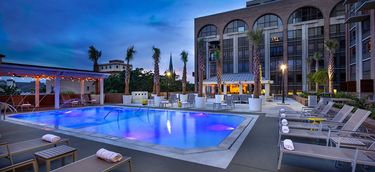 A modern outdoor pool that is lit up with blue lights, there are lounge chairs to the right and the hotel exterior in the background