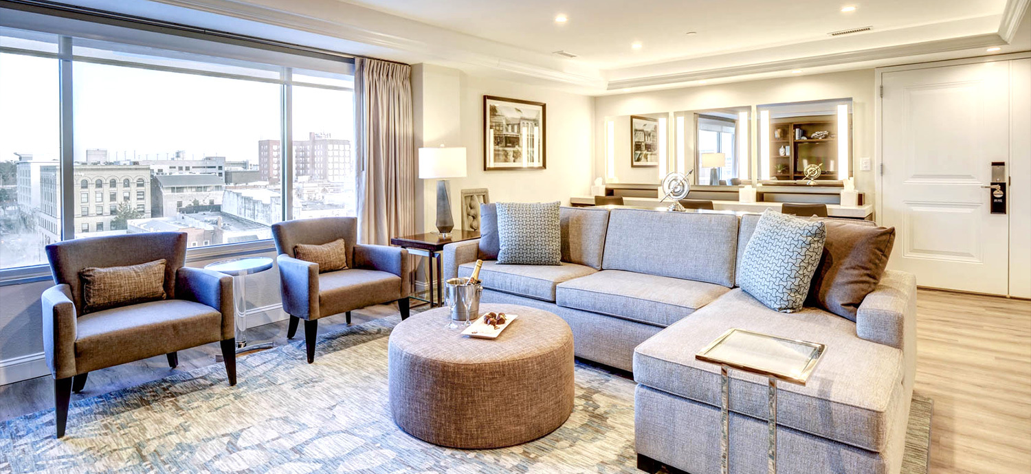 Gray L shaped couch and two armchairs with a rug and coffee table in a bright, cozily decorated hotel room