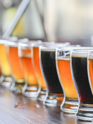 Row of glasses on bar filled with craft beers