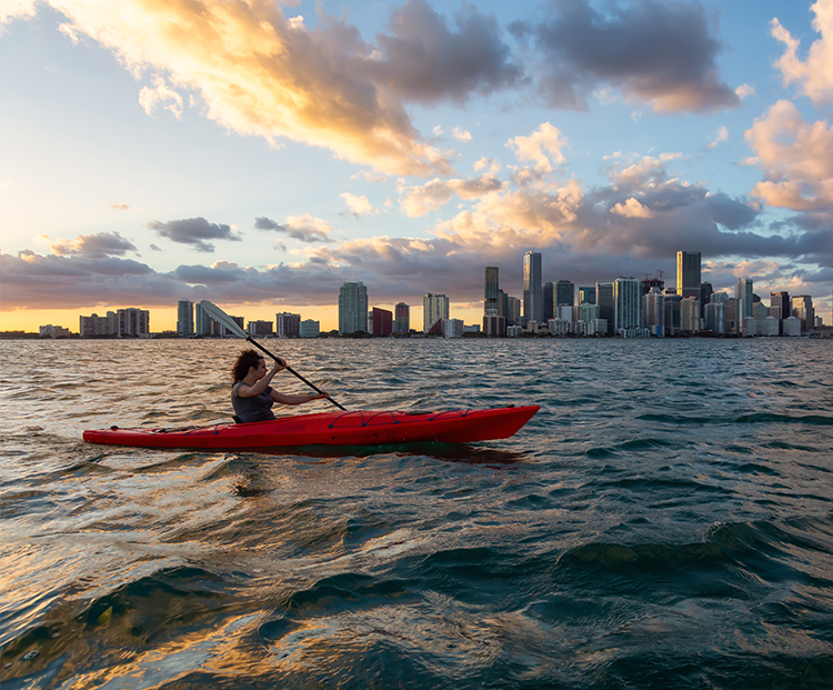 woman kayaking in the ocean with the miami skyline as a backdrop