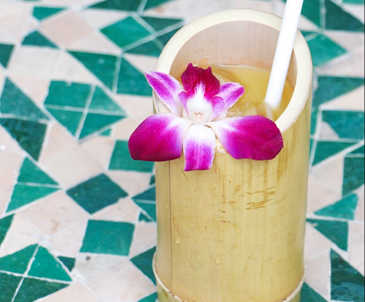 tropical cocktail in a tiki cup with a flower garnish