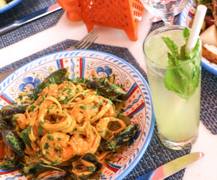 plate of pasta with shrimp on top next to a mojito cocktail