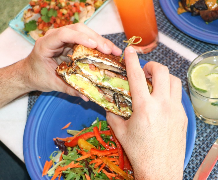 hands of a man holding a sandwich with a side of salad and citrus cocktail