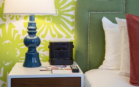 nightstand with a blue lamp and alarm clock
