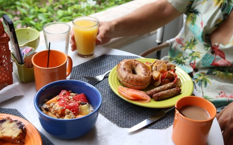 breakfast table with fruit, orange juice, coffee, and bagels