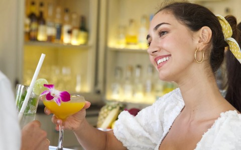 young woman smiling while holding a cocktail