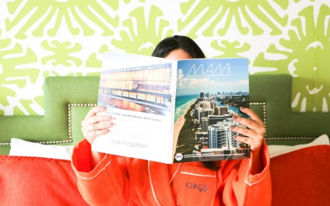 woman reading miami magazine holding it up to her face