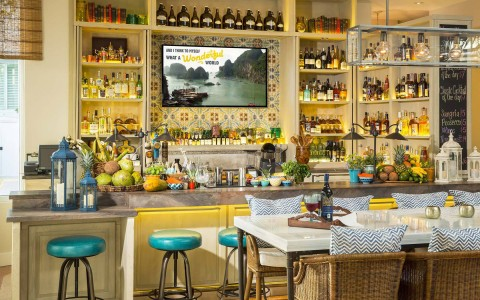 Bar with colorful tile decor, blue stools, fruits for garnishes and shelves with a variety of liquor