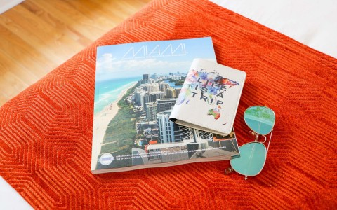 miami magazine sunglasses and passport on a bed