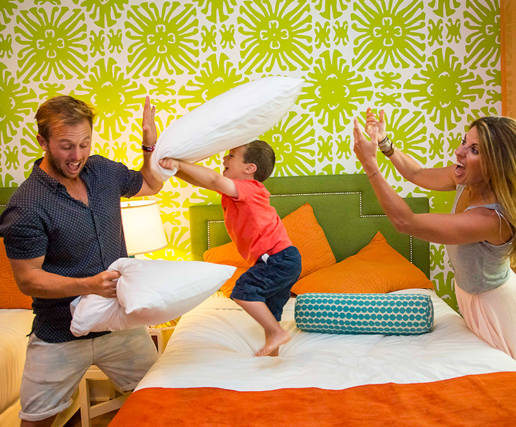 son playing pillow fight on top of the bed with mom and dad