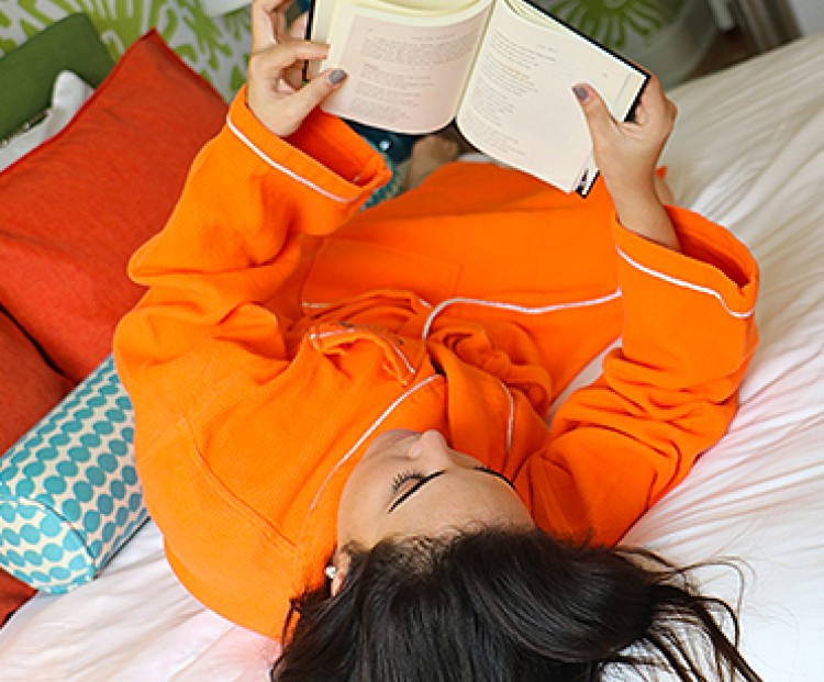 woman reading a book on a bed wearing an orange robe