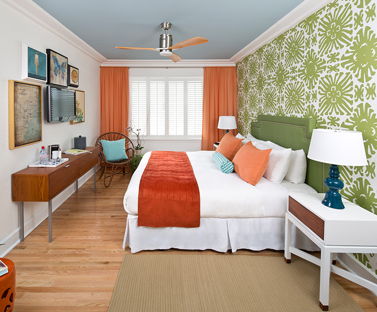 circa 39 king bedroom with green textured wall paper and orange drapes
