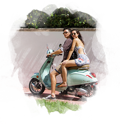 man and woman riding a  sea foam colored scooter
