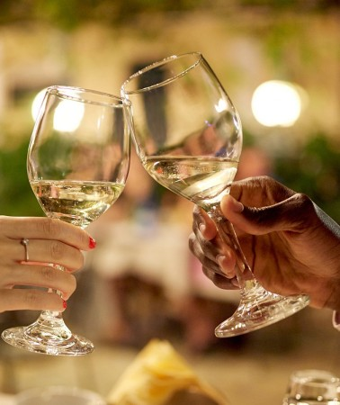 close up of a couple holding their glasses of white wine together for a cheers at dinner