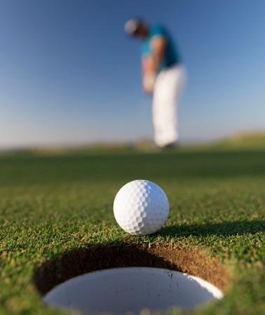 close up of a golf ball about to go into the hole