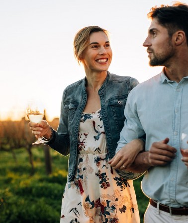 man and woman holding wine glasses walking in a vineyard through a vineyard