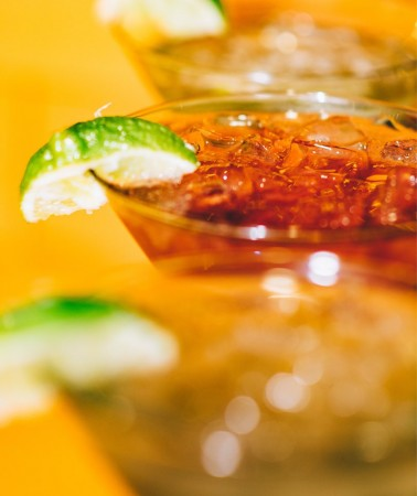 close up of a row of cocktails with lime slices on the rim