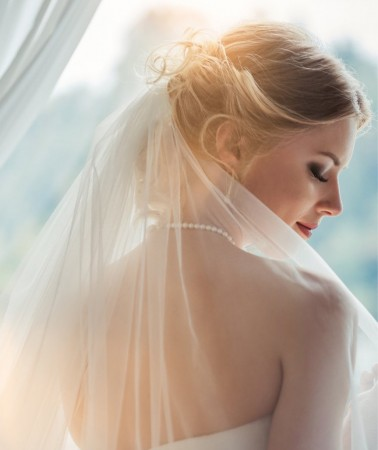 a bride facing the window with her head turned to the side showing off her veil