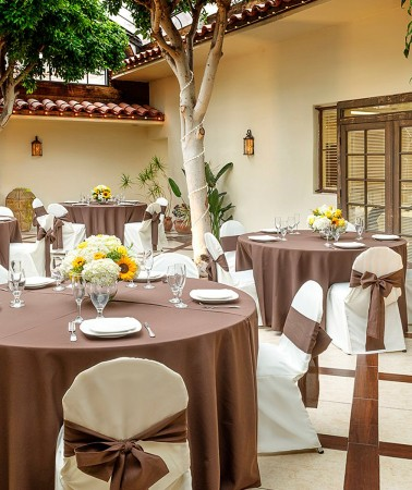 atrium outdoor venue space with round tables with brown tablecloths and white chairs