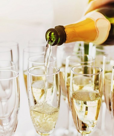 a person pouring champagne into rows of champagne glasses