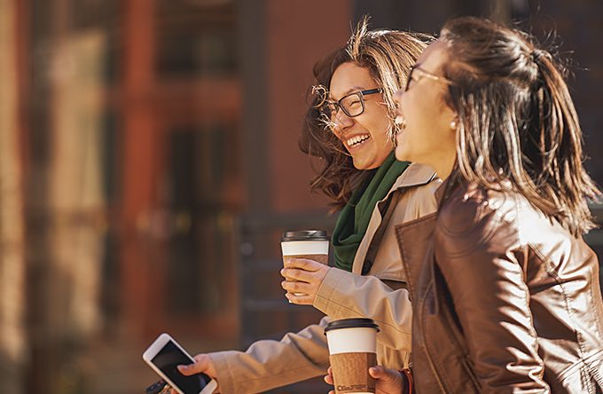 two women walking with coffee