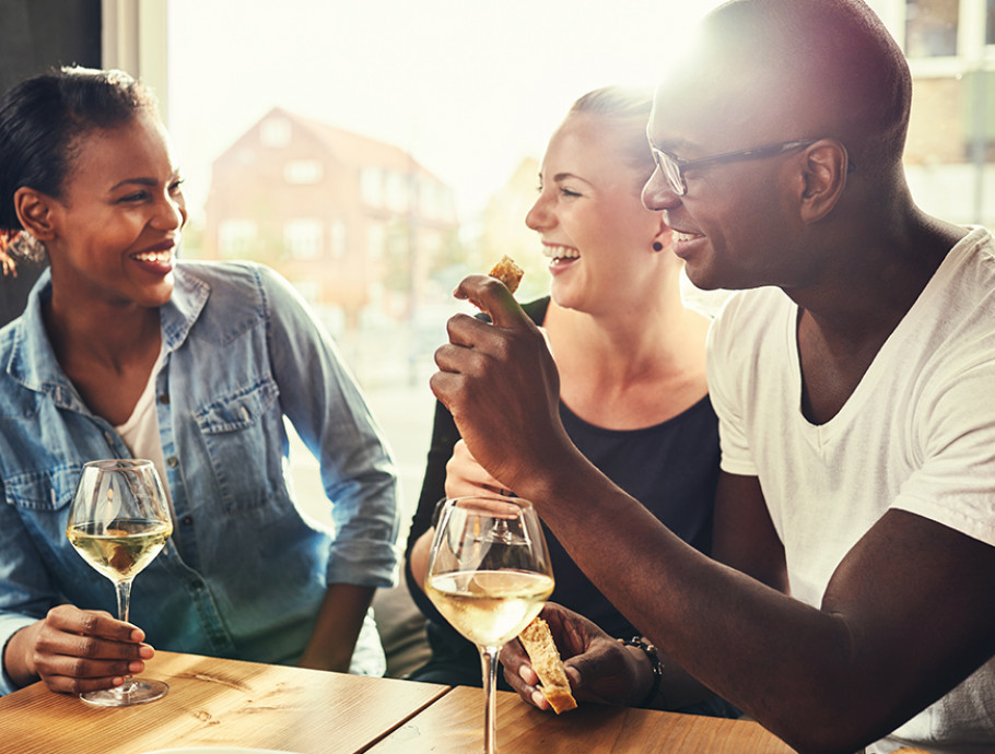 three people laughing and enjoying wine