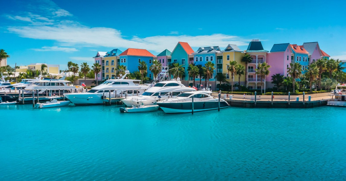 Small yachts docked on harbor with colorful buildings in the back