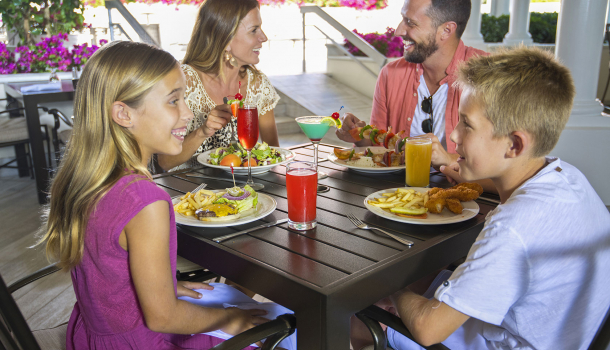 Family having breakfast outside next to breakfast bar with fruits