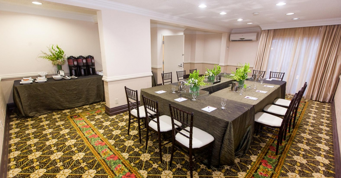 Room set with tables for meeting with notepads & refreshments