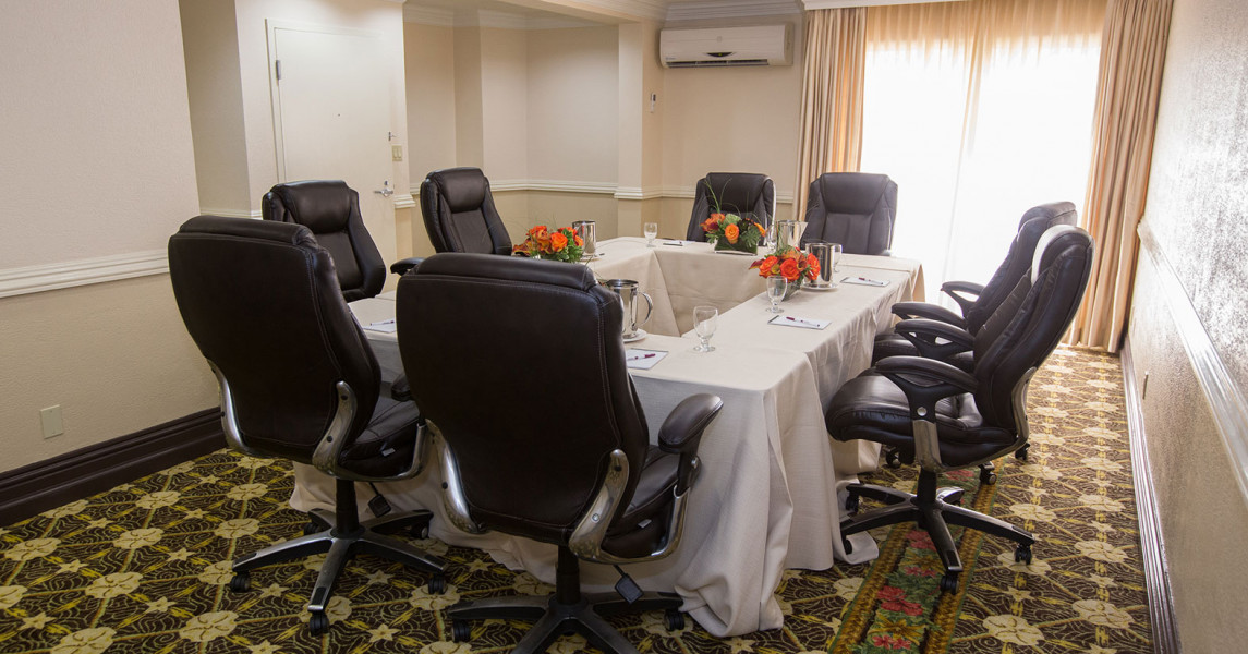 Meeting room black chairs around rectangle table set up