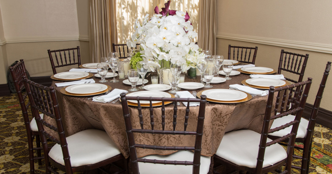 Round table with white chairs and white dishes and large bouquet of flowers in center