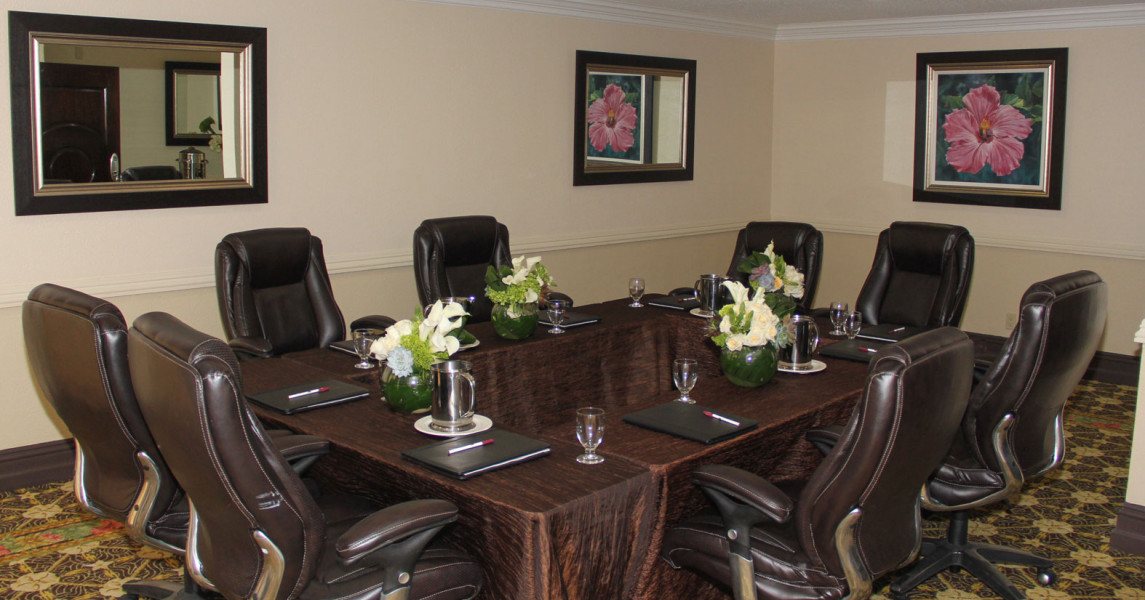 Black chairs around a board room table with brown tablecloth