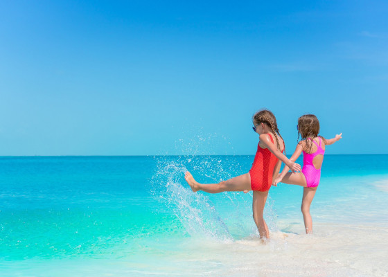 Two girls kicking their feet in the water on the beach shore