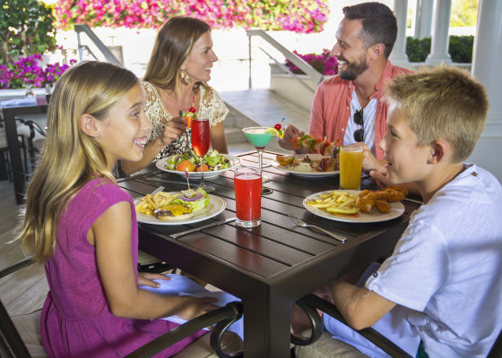 family of four eating at table smiling