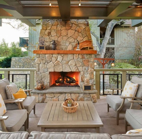 outdoor fireplace on a covered patio with comfortable seating