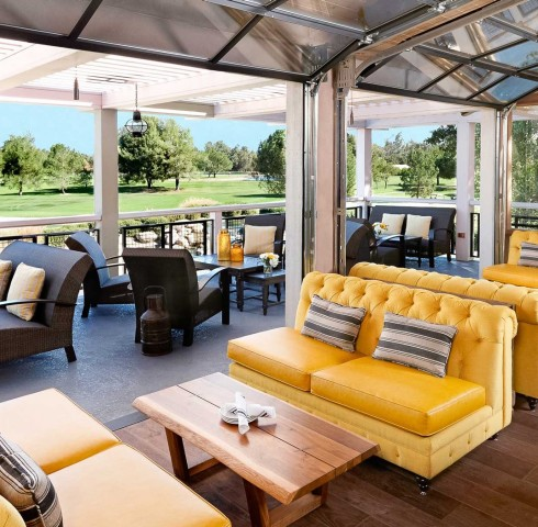 yellow and blue couches on a covered outdoor patio overlooking the golf course