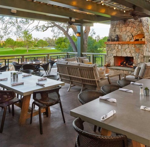 covered outdoor patio dining area with a view of the golf course
