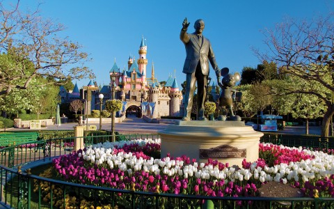 statue of walt disney and mickey mouse with disneyland castle in background