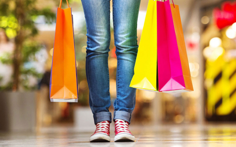 person in jeans holding shopping bags pictured from legs down