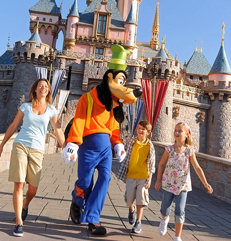 Woman, two kids and Goofy walking in front of the Disney castle