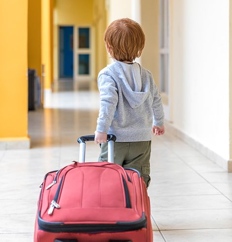 Young boy pulling a red suitcase behind him