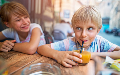 Two young kids one drinking juice