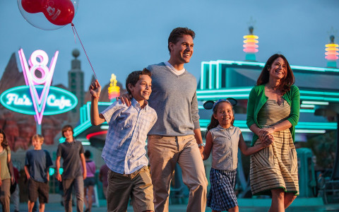 Man, woman and their two kids with neon lighted buildings behind them