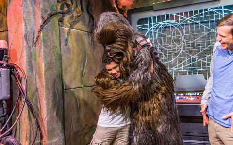 Boy getting a hug from Chewbacca character