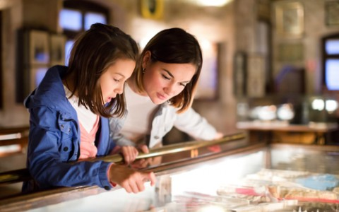 mother and daughter looking into glass case at museum